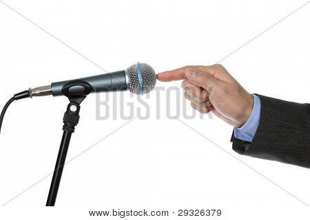 Businessman testing a microphone about to make a speech at a press conference