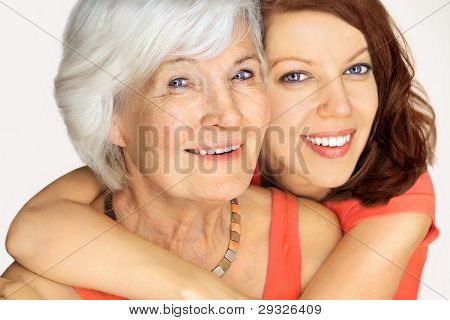 Grandmother and granddaughter portrait, embraced  on white background