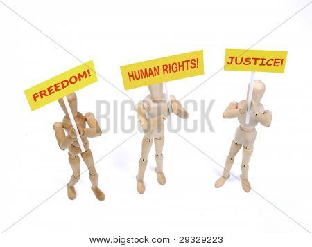 Three wooden dummies as demonstrators holding placards saying - Freedom, Human Rights and Justice shot on white background