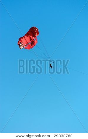 People Parasailing Against A Clear Blue Sky