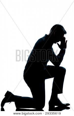 one caucasian man kneeling full length silhouette in studio isolated white background
