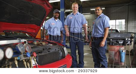 Portrait of three auto shop mechanics