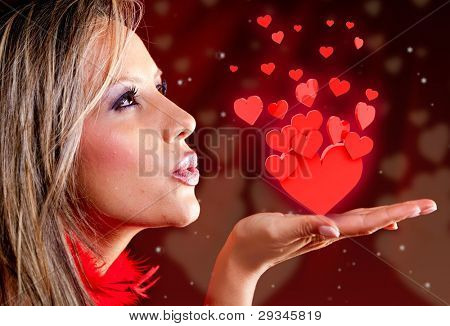 Woman celebrating Valentines day blowing red hearts