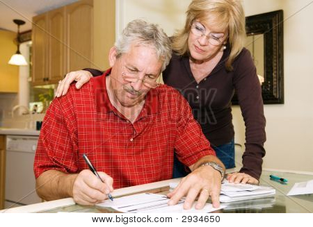 Mature Couple - Signing Paperwork