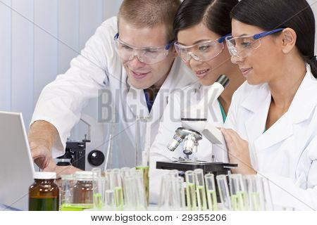 Interracial team of male and female medical or scientific researchers or doctors using a laptop & microscope in a laboratory.