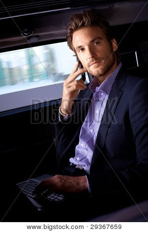 Handsome young man sitting in limousine, working on laptop computer, talking on mobile.?