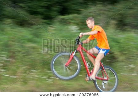Cyclist Extreme Riding A Bicycle. The Image Is Not In Focus