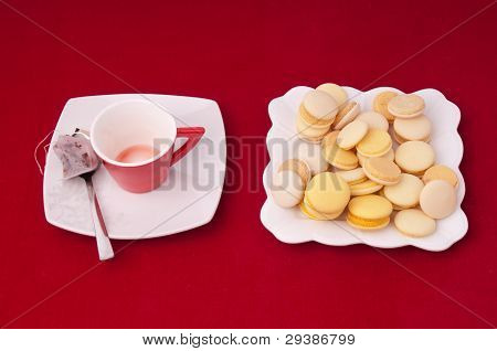 Empty Cup Of Tea And Plate Of Mixed Macaroons On A Velvet Tablecloth.