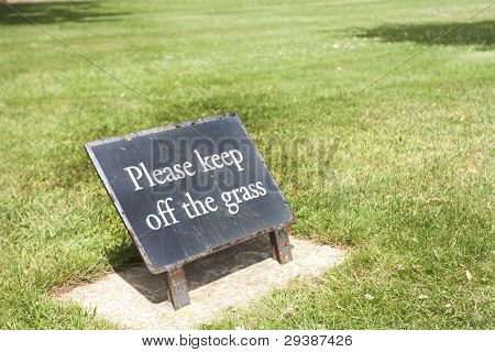 please keep off the grass sign on the grass in summer