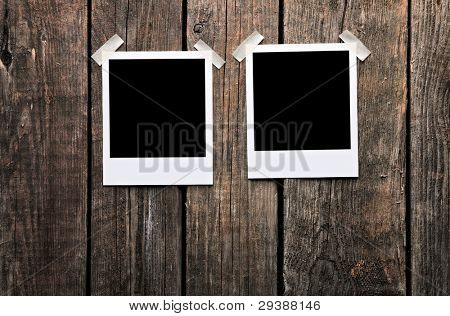 Blank instant photo frames on old wooden background.