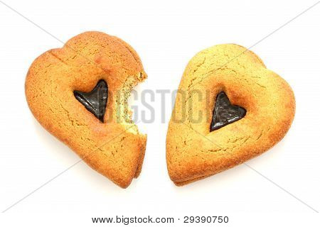 Gingerbreads in heart shapes one partially bitten on white background