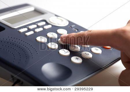 Man's hand dialing telephone keypad,