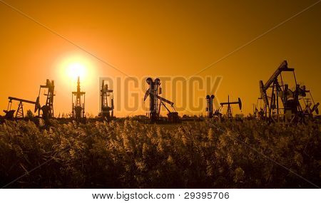 Silhouette of oil pump with sunset on the prairie