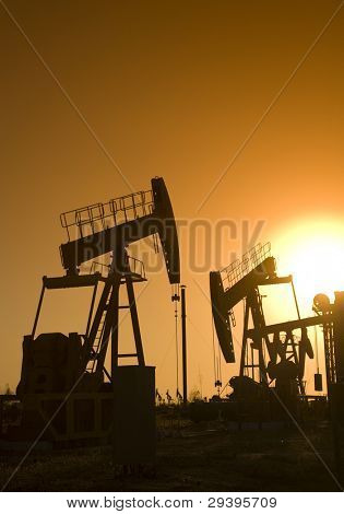 Silhouette of oil pump jack with sunset