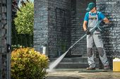 Driveway Pressure Washing. Caucasian Worker Cleaning Area In Front Of The House. poster