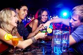 Image of happy girl looking at her glass while young man pouring cocktail into it with friends near