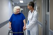 Front view of mature Caucasian  female doctor talking with a senior Caucasian female patient in clin poster