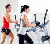 man and woman with elliptical cross trainer in sport fitness gym club