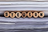 German Word For Tax. Detail Shot Of Steuern Word Between Stacked Documents poster