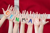 Denmark Inscription On The Childrens Hands Against The Background Of A Waving Flag Of The Denmark poster