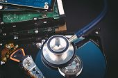 Data Recovery Or Computer Forensics Concept, Stethoscope Dusty Dismantle Hard Disk Over Dark Backgro poster