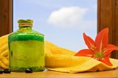 stock photo of belladonna  - Spa objects with red belladonna lily against blue sky - JPG