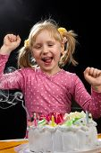 stock photo of party people  - Little girl blowing out candles in her birthday - JPG
