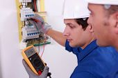 stock photo of fuse-box  - Two technical engineers checking electrical equipment - JPG