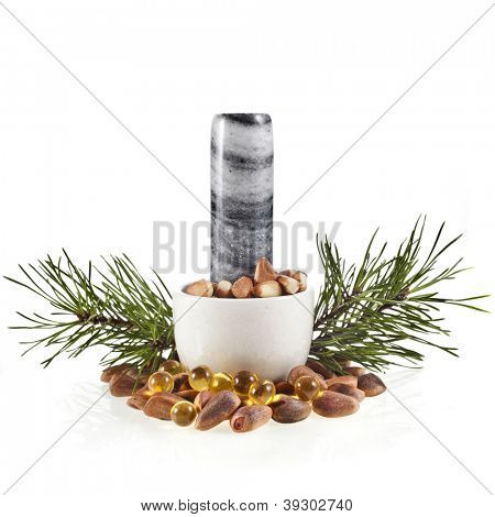 cedar pine nuts in a marble mortar and essential oil capsule isolated on white background