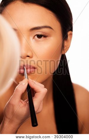 Beautfiul Asian woman applying lipstick from a long apllicator with the handheld mirror obscuring half of her face isolated on white