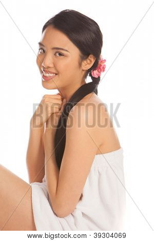 Beautiful Asian woman sitting on the floor in a short white towelling bath robe smiling prettily at the camera in a health and hygiene concept