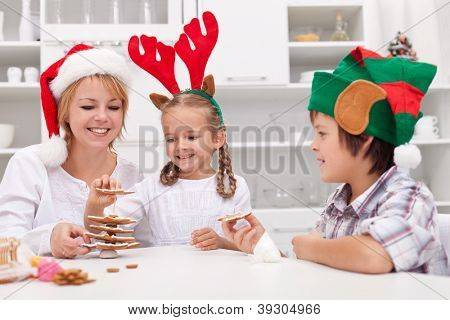 Happy family with seasonal hats making gingerbread christmas tree