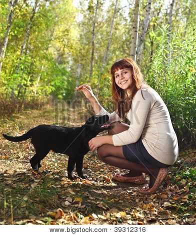 Teenager Girl And Black Labrador Retriever Puppy