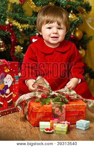 baby play with present box at Christmas tree