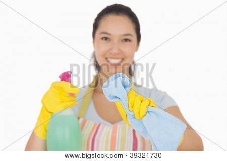 Happy woman in apron wiping with cloth in front of her