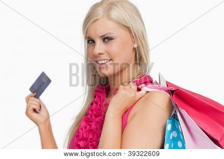 Smiling blonde holding credit card against white background