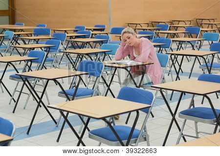 Blonde student studying at desk in empty exam hall in college