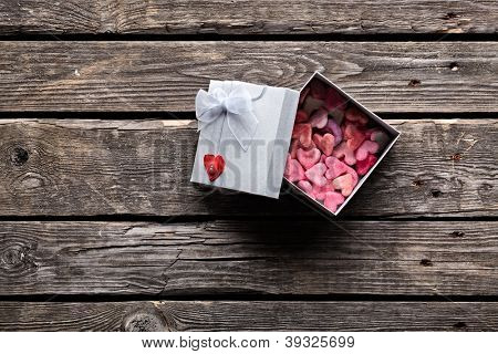 Open gift box with lots of cute little hearts inside. On old wood background.