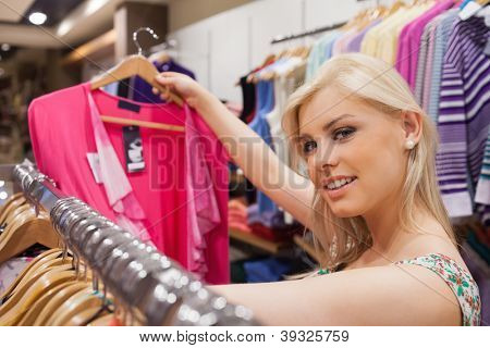 Woman is in a boutique while standing at a clothes rack looking at clothes