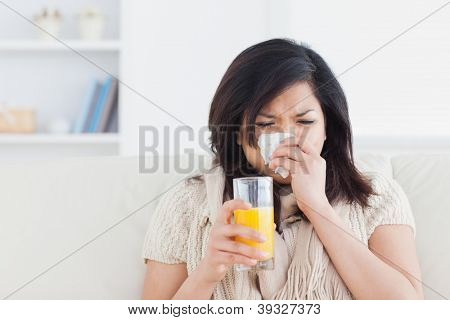 Sneezing woman drinking a glass of orange juice in a living room