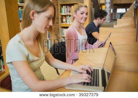 Woman using tablet pc looking up from studying in college library