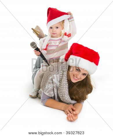 Baby Girl In Christmas Hat With Microphone Sitting On Mother Back