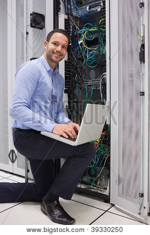 Man doing maintenance at the data store with laptop