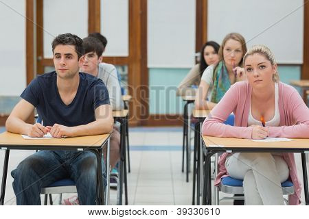 Students sitting at desk looking up in exam hall in college