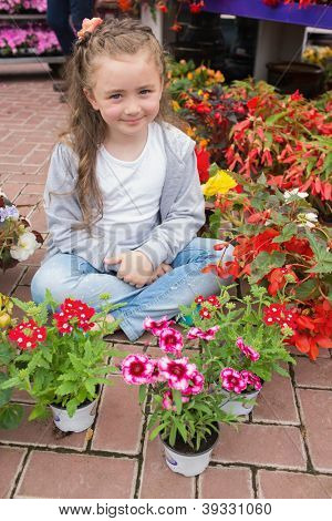 Little girl sitting on the floor with flowers around her in the garden center