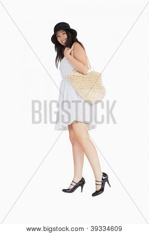 Smiling woman in polka dot dress with wicker bag turning away