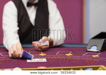Dealer sitting in a casino at table while holding and distributing cards