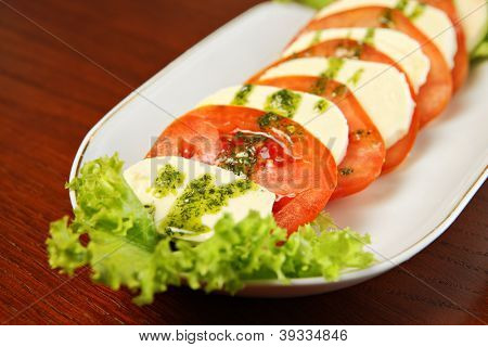 A picture of capresse salad over wooden background