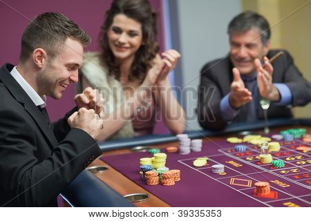 People cheering man at craps game in casino