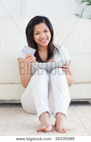 Woman holds a card and plays with a tactile tablet in a living room